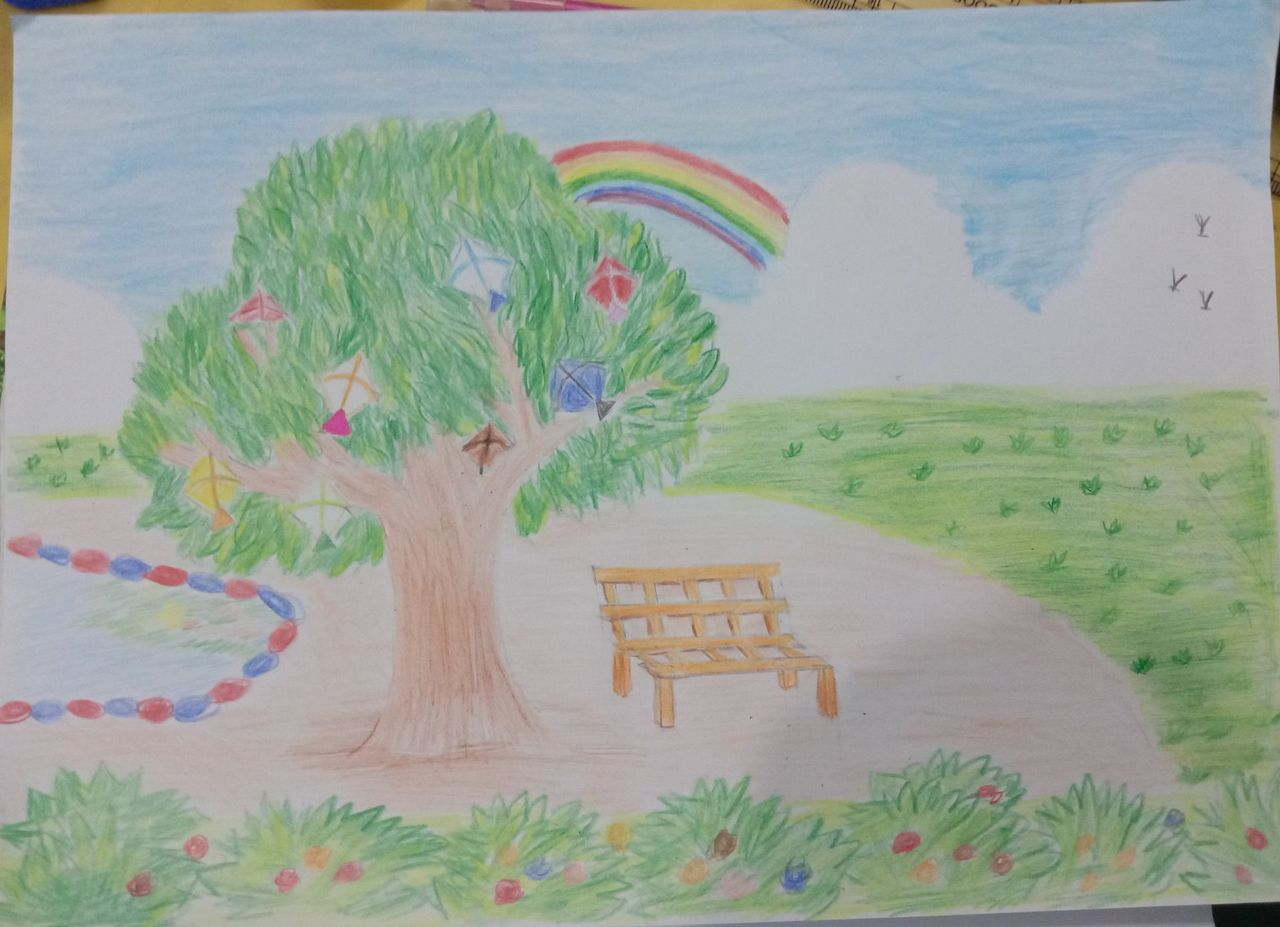 There is a tree beside a pond which is decorated with kites, colorful kites