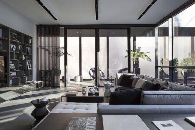 Um open espace com cozinha moderna e uma imensa sala, parede de vidro com a vista para as montanhas, uma lareira moderna posicionada à esquerda, sofás de couro espaçosos, tudo sóbrio e sofisticado