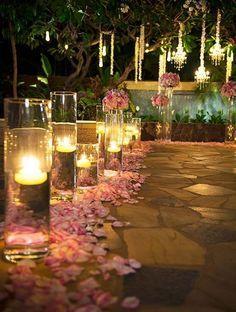 Eu vejo o lugar onde ele me pediu em casamento, um caminho com rosas vermelhas vai até o centro do jardim em um palco